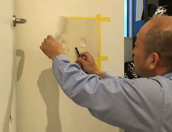 ①壁紙を傷部分より大きくコの字型にカッターで切り、テープで仮止めをする。